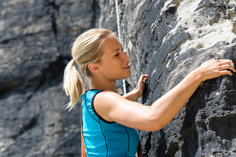 Rock climbing blond woman on rope sunny day