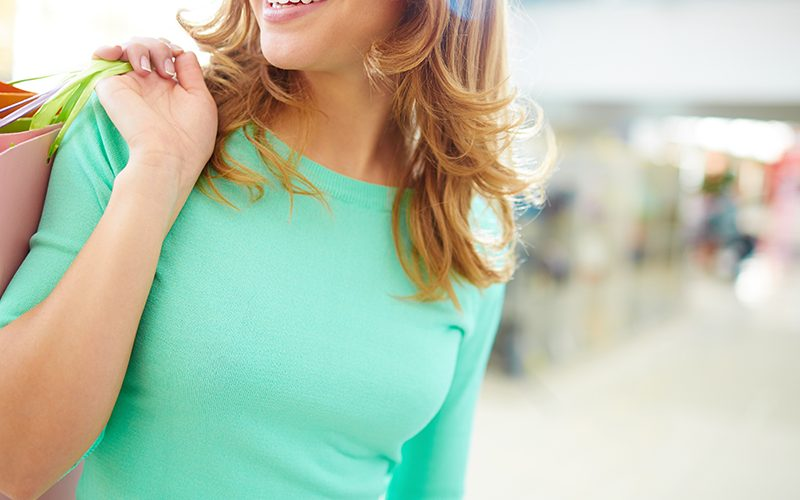 Close-up of smiling girl with shopping bags