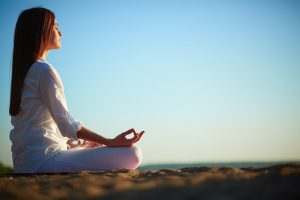 How to remain calm - side view of meditating woman sitting in pose of lotus against blue sky outdoors -