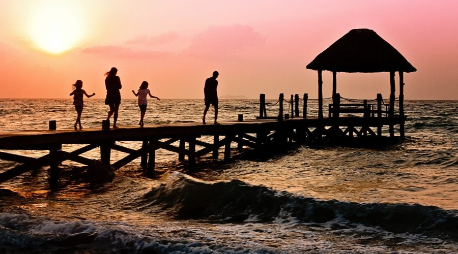 Family walking on pier at sunset